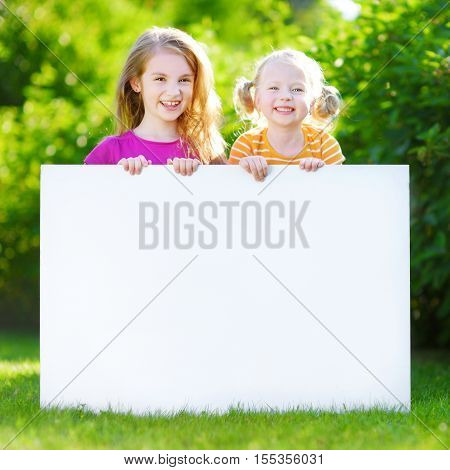 Two Cute Little Sisters Holding Big Blank Whiteboard