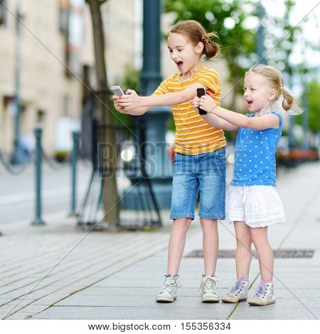 Two Cute Little Sisters Playing Outdoor Mobile Game On Their Smart Phones