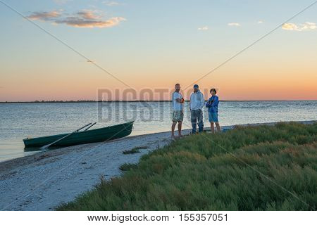Meeting of old friends - concept. Company of friends on the beach during sunset.