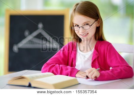 Smart Little Schoolgirl With Pen And Books Writing A Test In A Classroom