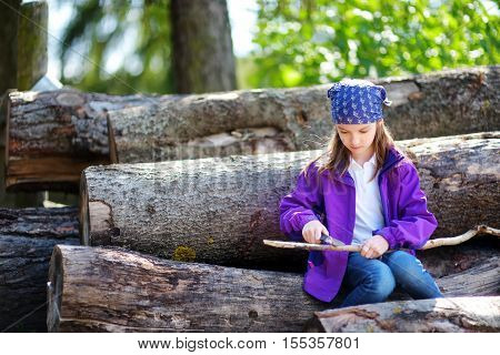 Cute Little Girl Using A Pocket Knife To Whittle A Stick For A Forest Hike