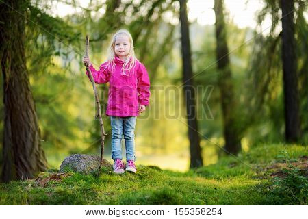 Cute Little Girl Having Fun During Forest Hike On Beautiful Autumn Day