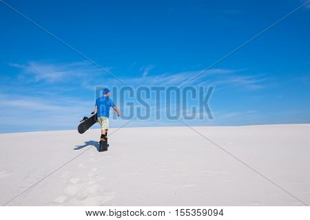 Sand boarding in desert. Rider comes up to the crest of a sand dune. Back view.