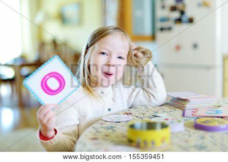 Funny Little Preschooler Girl Memorizing Letters
