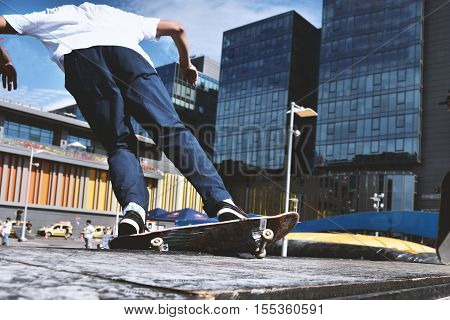 Skateboarding as extreme and fun sport. Skateboarder doing a trick in a city skate park.