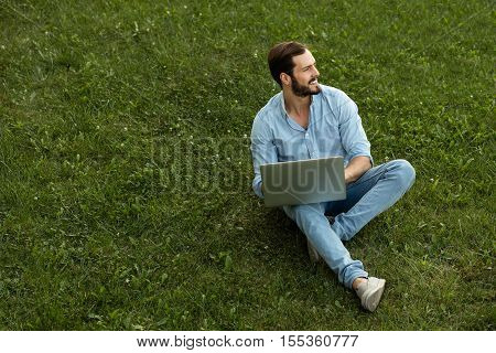 Young Man In Casual Jeans Outfit Lying Down With His Laptop In Front