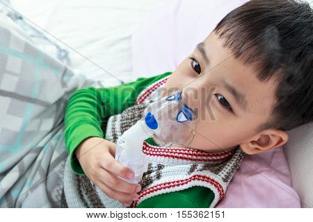 Top View Of Asian Child Holds A Mask Vapor Inhaler For Treatment Of Asthma. Breathing Through A Stea