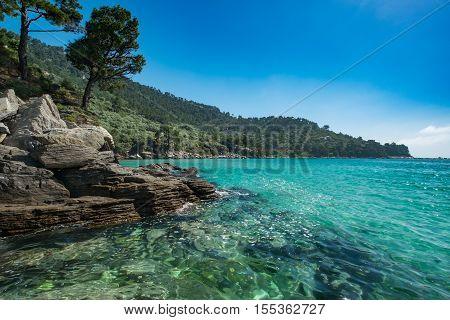 Beautiful rocky Greek coastline clear blue sea.