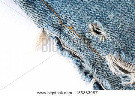 Lacking of jeans. Detail of blue denim jeans with old torn.