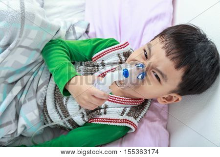 Top View Of Angry Asian Child Holds A Mask Vapor Inhaler For Treatment Of Asthma. Breathing Through