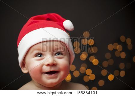 Happy smiling baby in Santa hat against black background