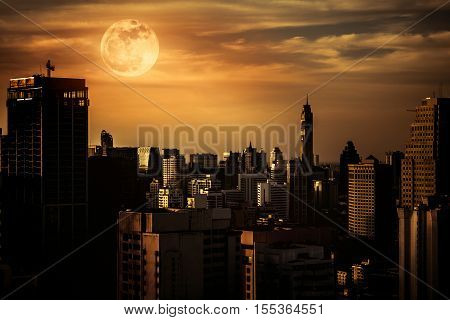Silhouettes Of Skyscrapers Different  Construction With Background Of A Large Moon At Nighttime.