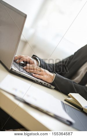 Pair of hands of unidentifiable man in suit typing on laptop keyboard at 45 degree angle with copy space.