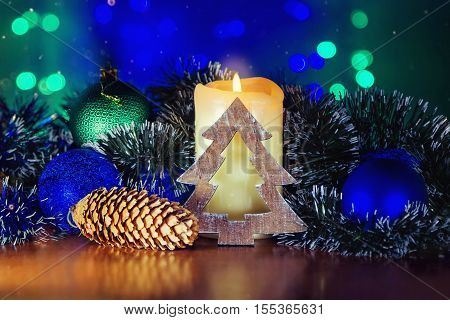 Burning candle and Christmas decorations on the table - sparkling balls, wooden christmas tree figure and tinsel on garland blue and green lights background