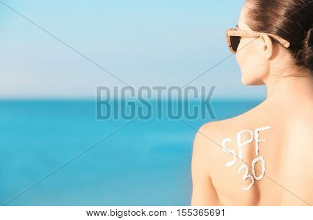 Text SPF 30 drawing on female shoulder