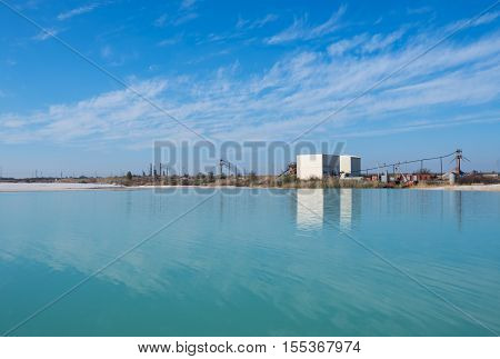 Industrial landscape. Factory on the shore of lake on the background of blue sky. Sunny autumn day. Wide angle.