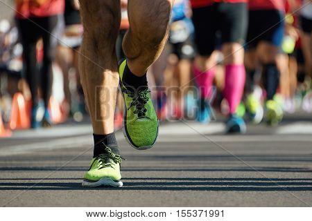 Marathon running in the light of evening, people feet on city road