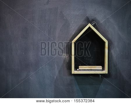 Hanging box of eraser and chalk on chalkboard background.