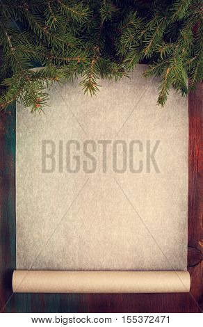 Christmas background with baking paper Christmas tree branches. top view (dark toning)