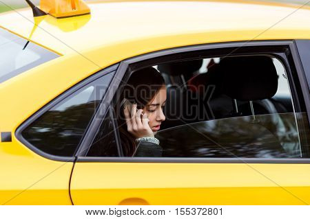 Portrait out the window young brunette lady riding in classic yellow cab and talking to someone on mobile phone