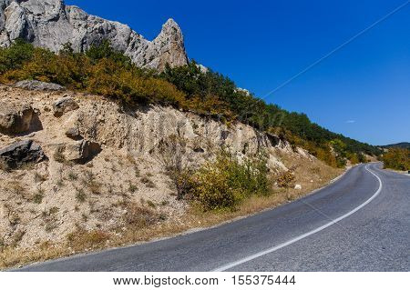 Russia. Crimea. Sudak. 13.09. 2016 Winding road at foot of mountains with autumn trees