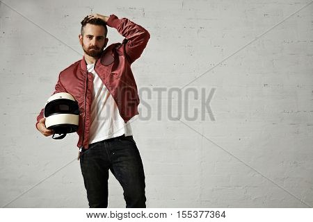 Tired young motorbiker in red bomber jacket, black jeans and white t-shirt adjusting his hairstyle and holding his white helmet