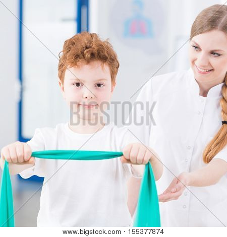 Pediatric Physiotherapist Exercising With Boy