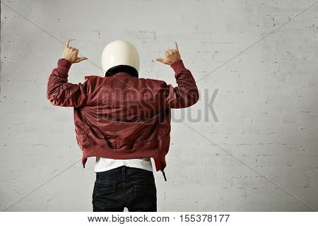 Man in jeans, white t-shirt, white motorcycle helmet and bomber jacket gesturing shaka with his hands, back shot