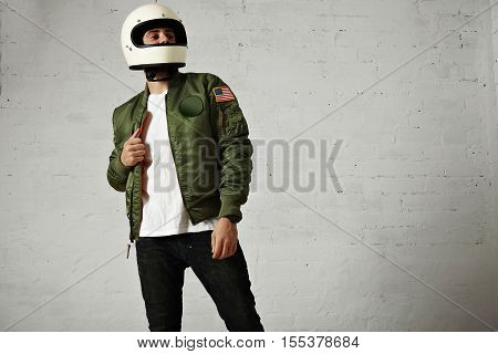 Proud looking motorbiker in a plain white helmet, khaki bomber jacket, jeans and t-shirt against white wall background
