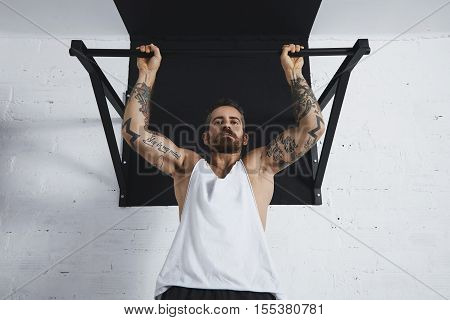 Strong tattooed in white unlabeled tank t-shirt male athlete shows calisthenic moves close up Pullup hold on medium move on pull bar