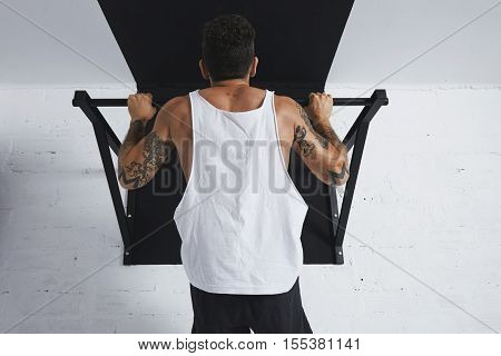 Back view on muscular male athlete in white blank tank t-shirt showing calisthenic moves Pull up on pullbar, holding on top