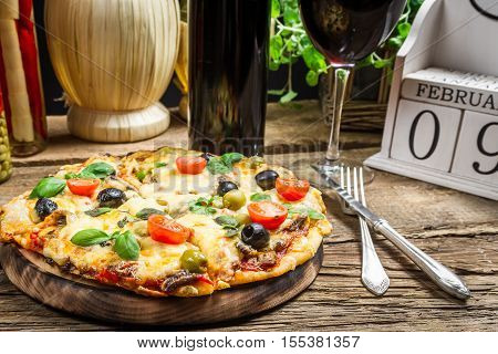 Freshly pizza served with red wine on old wooden table
