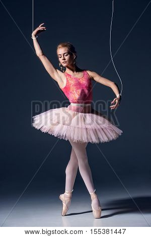 The ballet dancer as puppet dancing over gray background