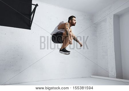 Bearded and tattooed young male athlete shows calisthenic moves, jumping high in air, isolated in white room of fitness center
