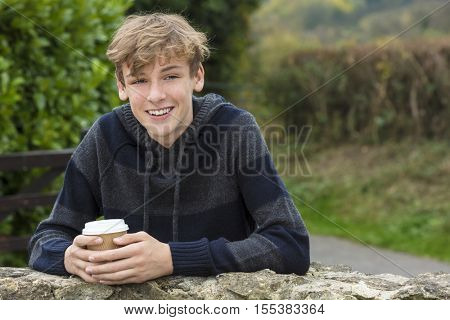 Young happy laughing male boy teenager blond child young adult drinking takeaway coffee outside in fall sunshine