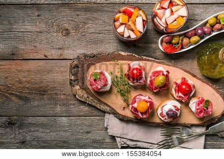 spanish tapas and sangria on wooden table, top view ith copy space