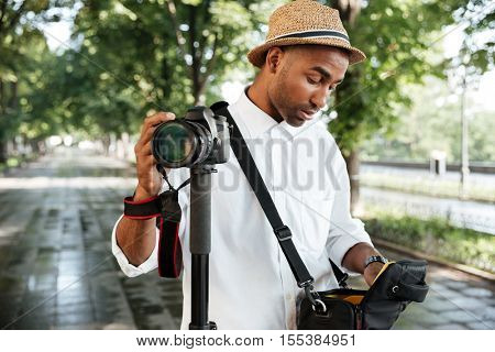 Hipster in park. photographer. with hat. black man