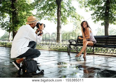 Photographer takes photo of young beautiful brunette woman in park. afro photographer