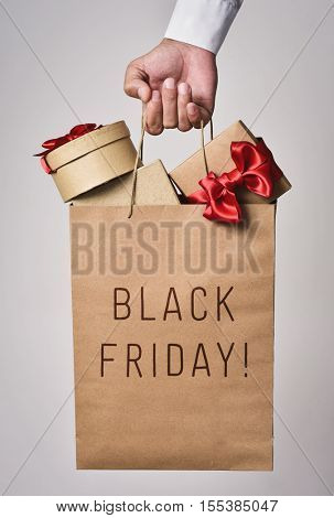 closeup of a young caucasian man with a paper shopping bag full of gifts in his hand and the text black friday written in it