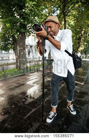 Young black man in park. full lenght. with camera