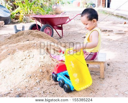 Thai baby boy palying on pile of sand with toy and plastic fork spoon truck wheel barrow
