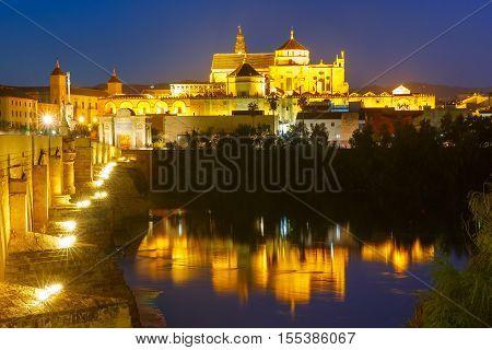 Illuminated Great Mosque Mezquita - Catedral de Cordoba with mirror reflection and Roman bridge across Guadalquivir river, Cordoba, Andalusia, Spain