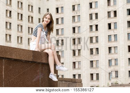 Young beautiful woman sitting on the stairs, near the university