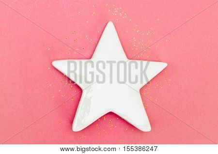 White ceramic star on pink background with golden star-shaped glitter. Space for text.
