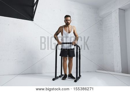 Strong tattooed in white unlabeled tank t-shirt male athlete shows calisthenic moves Extended legs plance push ups on parallel bars