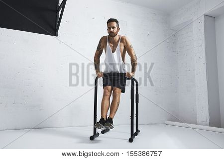 Strong tattooed in white unlabeled tank t-shirt male athlete shows calisthenic moves Straight dips move three, dip out on one of parallel bars