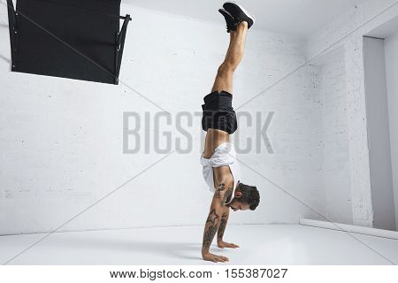 Strong tattooed in white unlabeled tank t-shirt male athlete shows calisthenic moves Handstand position
