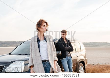 Young travelers couple standing near car outdoors on the field