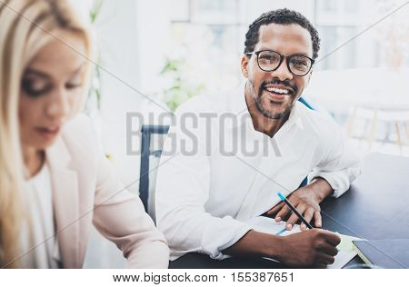 Two young business people working together in a modern office.Black man wearing glasses, looking at the camera and smiling.Businesswoman discussing with colleague new project.Horizontal, blurred