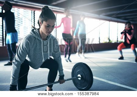Fit healthy woman lifting a weight barbell from floor exercising with group of people outside urban setting